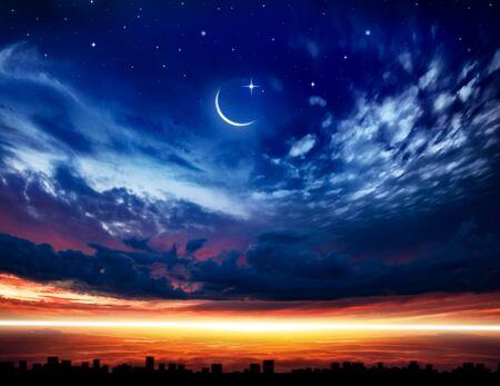 Beautiful dark fluffy cloudy sky with sun rays. Crescent moon with beautiful sunset background. Generous Ramadan. New moon. Prayer time.