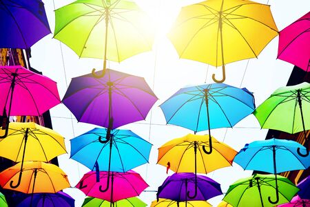 Umbrellas in the air. bright small streets of the city. Overcast weather. Rainy weather