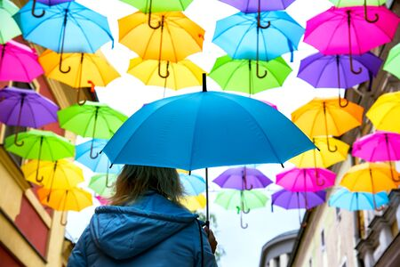 Umbrellas in the air. bright small streets of the city. Overcast weather. Rainy weather Stock Photo