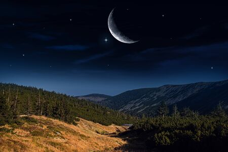 Moon above a mountain top. Beautifully summer landscape. Crescent moon with beautiful sunset background. Generous Ramadan. Light from sky. Religion background.