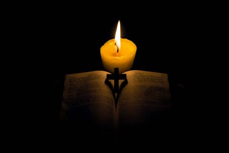 Burning candle and Bible. The psalms. Holy book. told in the Bibles New Testament, on a black background. Christian cross Stock fotó