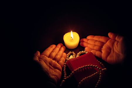 Praying hands, Islamic background. The holy Koran under candlelight. Book in candlelight