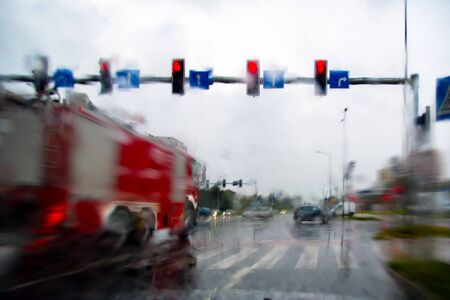 Fire truck. Go to the red light of the traffic light. Rainy day