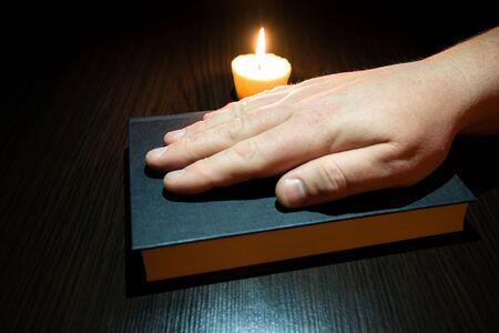 Een mannenhand op de Bijbel. Kaars op tafel. Stockfoto
