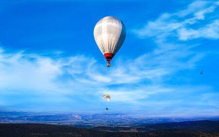 Ballon fliegt neben Fallschirm. Extremsport. Standard-Bild