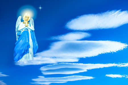 Angel in the clouds. Blue sky with clouds. religion background Foto de archivo