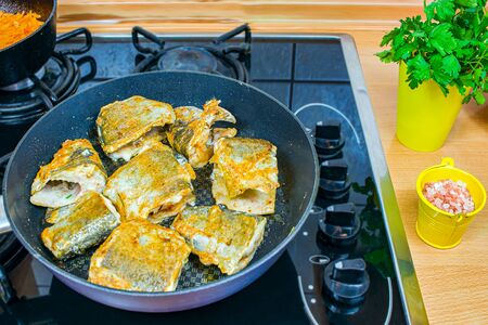 Fry the fish in the pan. Cooking at home. Diet fish with vegetables