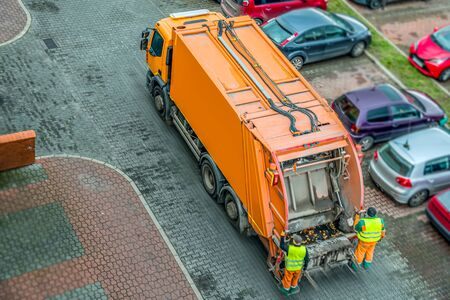 Urban recycling waste and garbage services. Orange truck, garbage removal. Stock Photo
