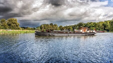 Trawler navigating a rive. Cargo ship. International logistics. Delivery of cargo by river Stock fotó