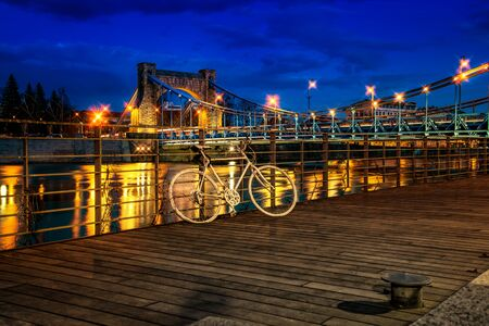 Grunwaldzki Bridge. Bicycle on the embankment of the night city Standard-Bild - 147827402