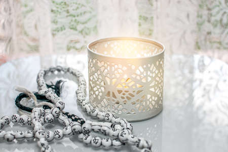 Prayer time. candle and rosary on the table Stock Photo