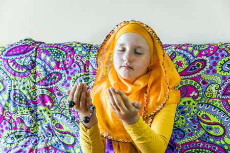 Muslim girl prays at home alone. background of regia teachings