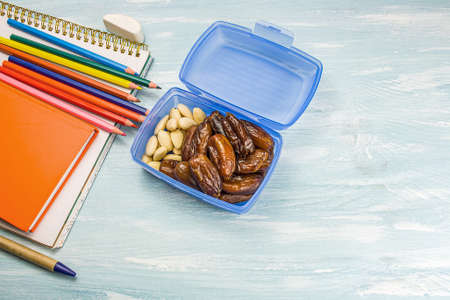 School supplies on a blue background. healthy nutrition for children in school Фото со стока
