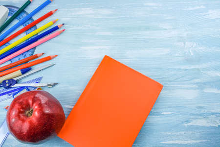 School supplies on a blue background. take a snack to school like an apple