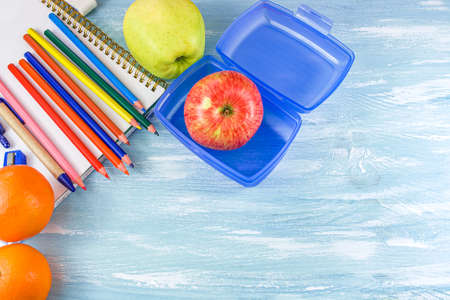 School supplies on a blue background. take a snack to school like an apple Фото со стока