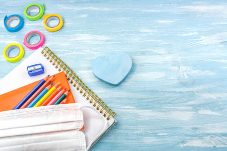 School supplies on a blue background. take a medical mask to school