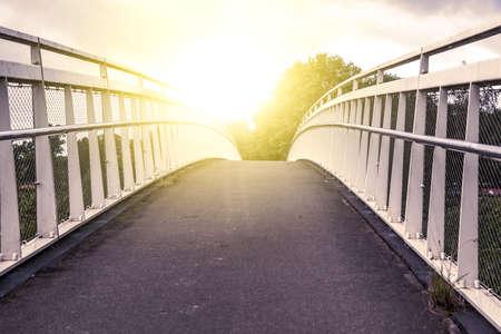 road on the bridge opposite sunlight