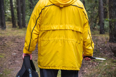 man in a yellow jacket in the woods, view from the back
