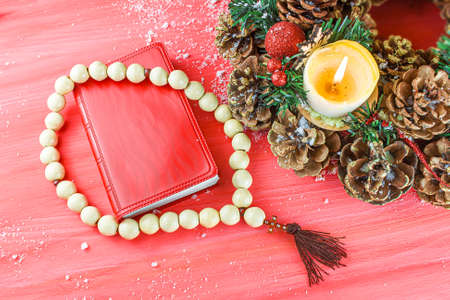 Christmas red background with Bible and rosary on the table, place for promotional text