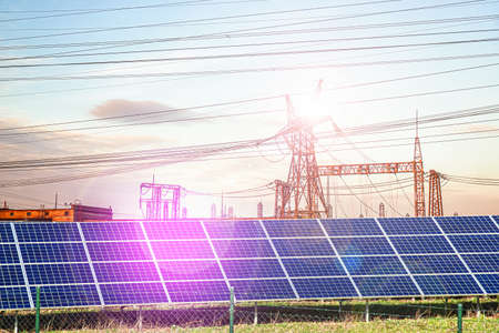 Solar panels with electricity pylons at sunset, Stock fotó