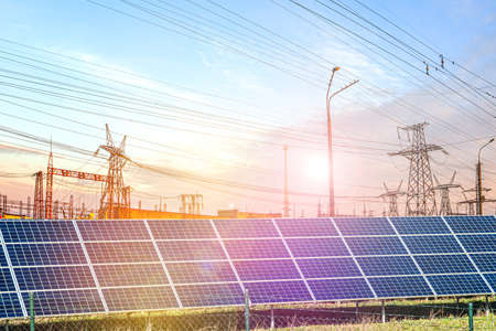 Solar panels with electricity pylons at sunset,