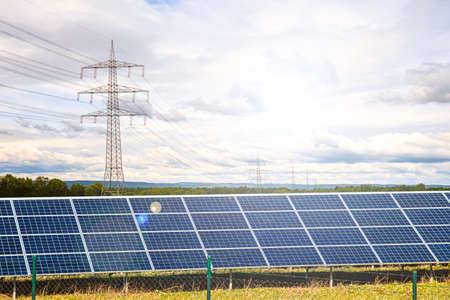 Solar panels with electricity pylons at sunset, natural resources Stock fotó