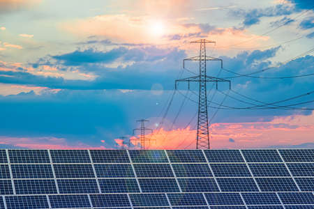 Solar panels with electricity pylons at sunset, natural resources