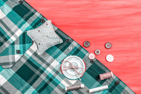 Accessories for sewing, threads and buttons on a red background