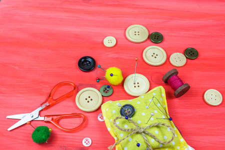 Clothing accessories, thread scissors and buttons on red background