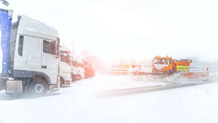 Winter service in action on the motorway, heavy snow on the roads, a ban on driving
