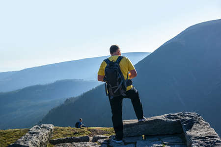 a man with a backpack on top of a mountain