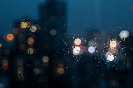 Abstract bokeh night light in city background. Night city through rain window. Defocused background. Reklamní fotografie