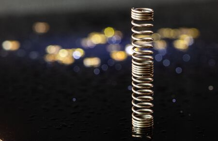 Metal spring. Precision mechanical parts. Twisted wire. Gold and silver bokeh. Part of the pen. Gold flares. Black background. Objects on a black background.