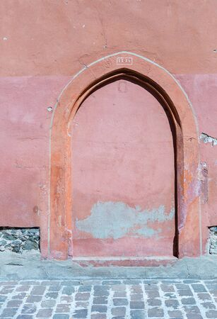 Wall and door of an old monastery. Peeling paint and plaster. Place of religious worship. Historic church. Wooden door The building needs renovation. Historic places. Interesting structure and surface.