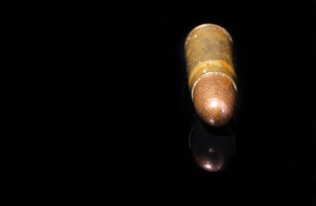 Pistol bullet. Metal case. Cartridge on a black background. Isolated from background.
