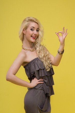 pantsuit: Emotional attractive young blonde woman standing in half length in brown pantsuit showing ok,  isolated on yellow background