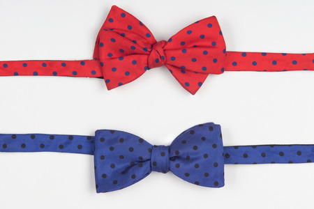 evoking: Red and blue dotted bow-ties, emphasizing the ambiguity of stile and evoking the curiosity to the identity of costume. Isolated on white background