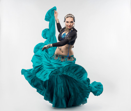 Exotic young belly dancer in the national costume is going to you  Isolated on the white background photo