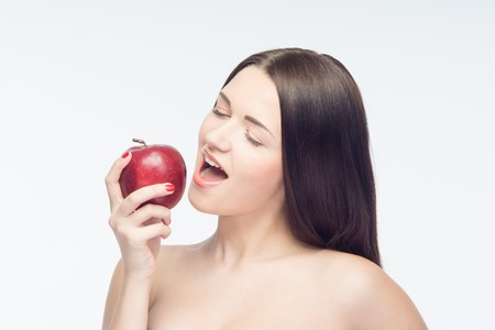 Eating of fascinating red tasty apple gets you feel better all day and gets your beauty attractiveness  Isolated on white background photo