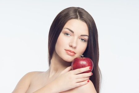 Red shine apple on shoulder of beautiful girl showing the result of eutrophy and healthy life-style  Isolated on white background  photo