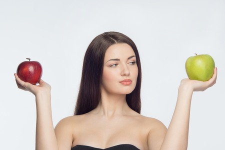 Half length portrait of very attractive girl holding red apple in one hand and green apple in another  Isolated on white background photo