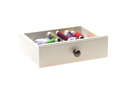 Drawer with different many-colored threads in it is the windfall for every housewife  Isolated on the white background photo