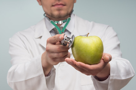 listened: Selected focus on the apple, which is listened  Doctor, wearing white uniform