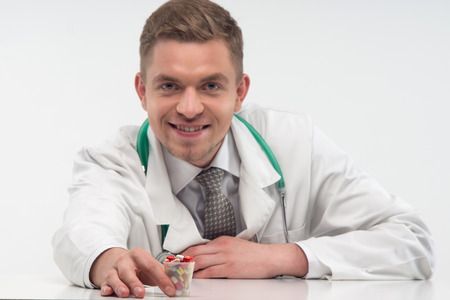 Young handsome smiling doctor, wearing beautiful tie and suggested us different colorful pills  Isolated on the white