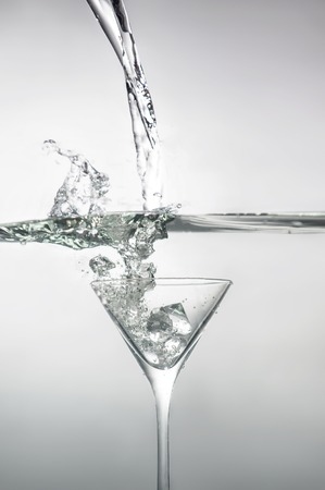 Great glass of martini with ice dipped into water with many bubbles photo