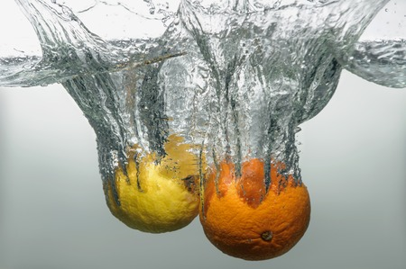 Orange and lemon falling down into the water with splash and little air bubbles photo