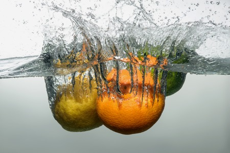 Tempting ripe orange, lemon and lime falling down into the water with big splash and bubbles photo
