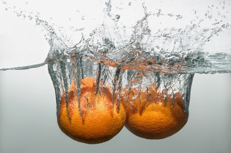 Two delicious ripe oranges dropped into the water with splash photo