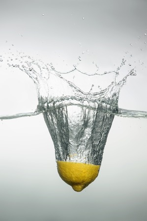 Tempting slice of lemon dropped into the water with splash and bubbles photo