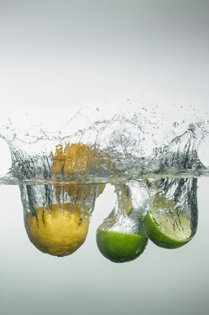 Halves of ripe citruses dropped into the water with a big splash  photo
